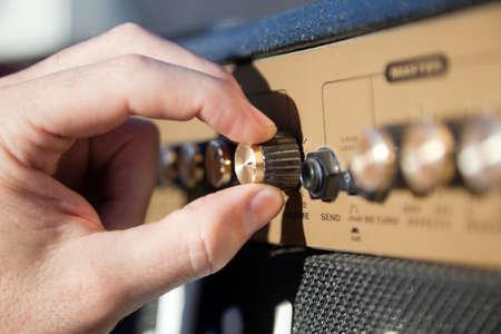 tremolo: Close up di una mano di controllo del volume di un amplificatore