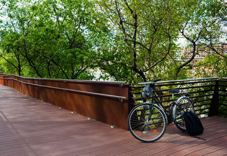 bicycle leaning against a fence with trees photo