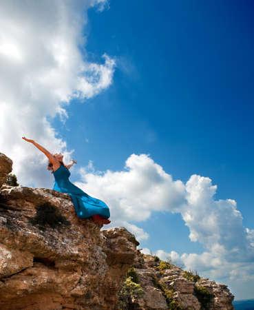 mujer mirando el horizonte: Niña con los brazos abiertos al cielo azul Foto de archivo