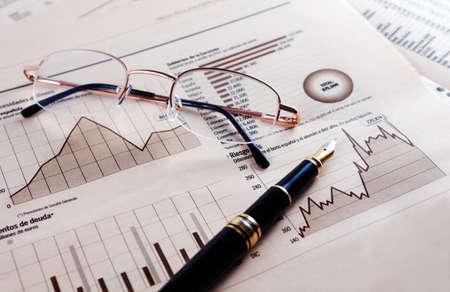 analyse: Business background avec des graphiques, des lunettes et un stylo