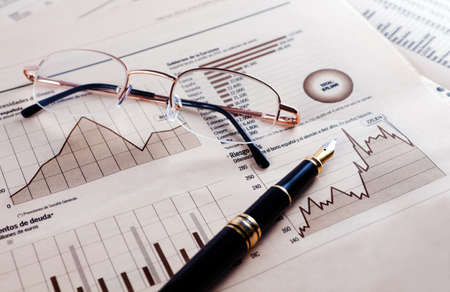 financial analysis: Business background with graphics,glasses and pen