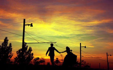 Sunset landscape and silhouettes of couple photo
