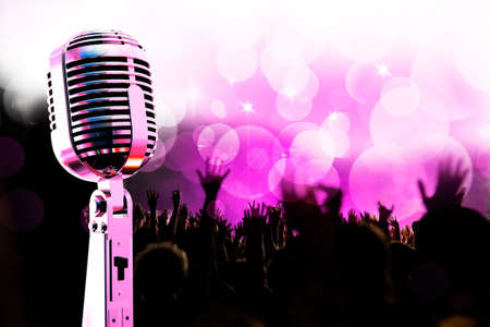 Live music background.Vintage microphone and public