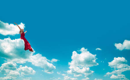Woman sitting on the cloud. Happiness and joy concept. photo