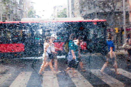 Abstract image of people walking in the rain in the city photo