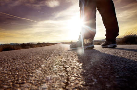 cross walk: anonymous man on the road and sunset landscape.travel concept