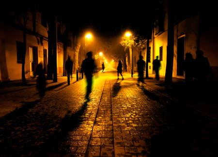 Miasto w nocy. Cienie ludzi idąc ulicą