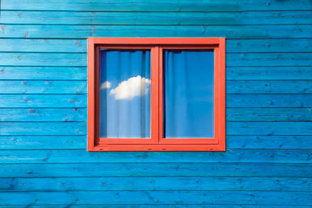 old house facade house: Modern colorful architecture. Wooden blue facade and red window  under blue sky Stock Photo
