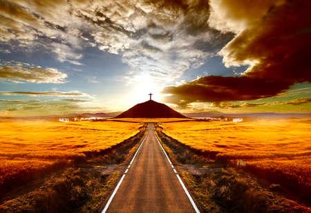 Avonturen en road trips.Sunset en travel concept.Road en kruis op de heuvel Stockfoto