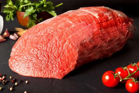 Still life raw beef round over black ground