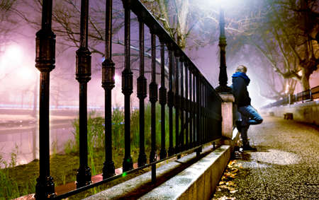lampposts: City street at night with trees,man and lamppost Stock Photo