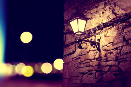 lampost: City lights and lamppost in the facade.Stone wall background at night