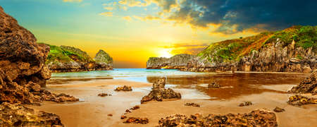 Stunning scenery of coastline,beach and cliffs in Cantabria, Spain. Vivid landscape of beach and coast with mountains and vegetation