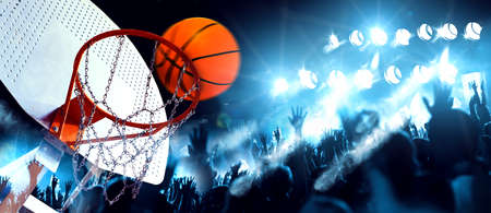 Hoop and ball illuminated by the spotlights. Competition and sport event. Public and crowd applauding the basketball game.Sports and entertainment. Basketball and team sports.