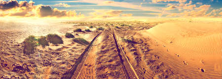 Sand desert landscape and road.Travel and adventures  in extreme nature.Tourism and scenic sunrise