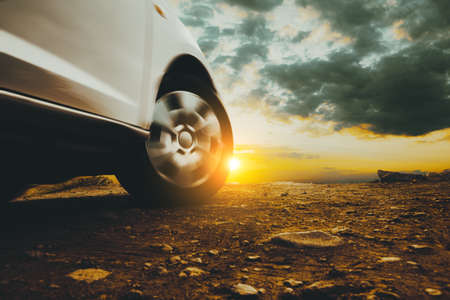 Closed image of car wheels and tires on the ground and sunset sky Archivio Fotografico