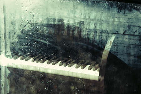 piano behind the window with water drops on a rainy day.Relax music for travel road. Archivio Fotografico