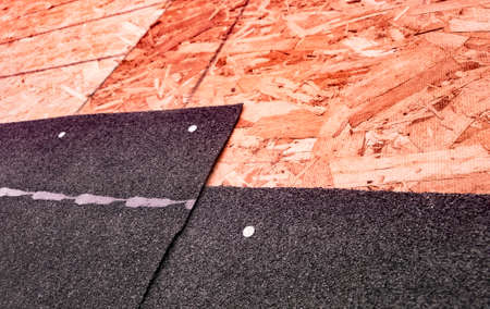 Closeup of overlapping black asphalt shingles and underlying oriented strand board subroof material Stock Photo