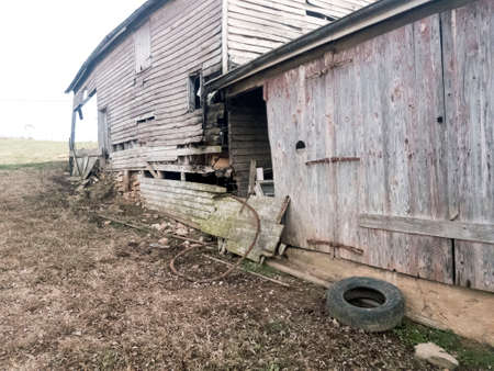 Dilapidated, abandoned wooden farm house and attached wooden garage Stock Photo