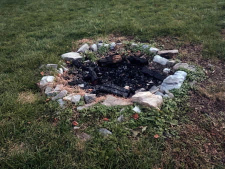Stone lined camp fire ring set into ground with burned remains of firewood