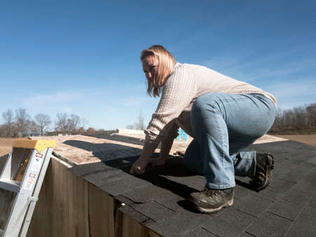 Smiling woman in jeans and sweater kneeling while shingling roof of animal shelter Stock Photo