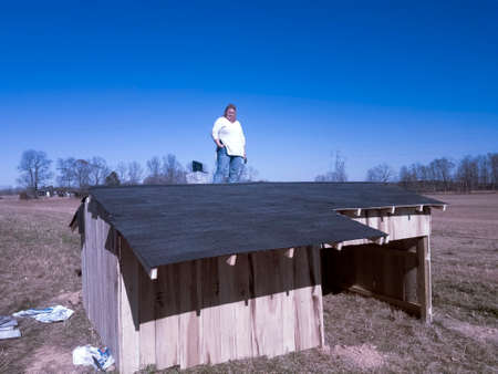 Smiling woman in jeans and sweater standing on roof of animal shelter