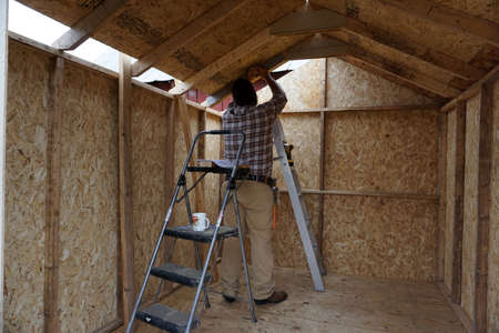 Construction worker in plaid shirt, tan pants, and knit hat installing interior of wooden shed Stock Photo