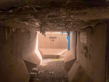 Interior of cement t-wall bunker with water bottles on ground Stock Photo