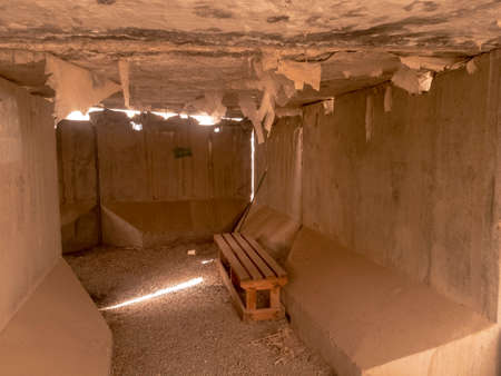 Interior of cement t-wall bunker furnished with wooden bench