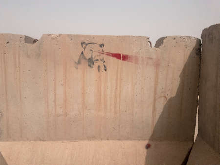 Stencil of bear with laser beams shooting out of eyes on cement wall