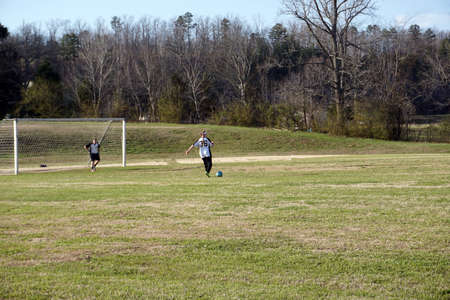 Two girls playing soccer in field