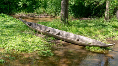 Dugout canoe prop on edge of water flow Stock Photo