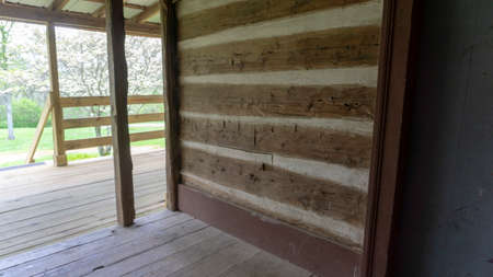 Section of log cabin wall made of hand hewed logs set in white mortar