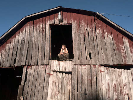 Young blonde girl in camouflage pants and green tank top crouching in hay loft doorway with eyes closed Stock Photo