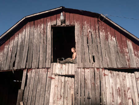 Young blonde girl in camouflage pants, green tank top, and rubber boots sitting in hay loft doorway looking off into distance Stock Photo