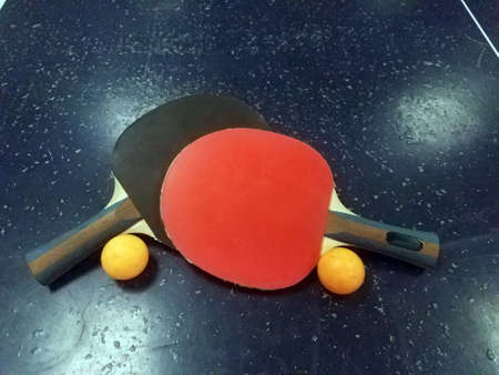 Red and black table tennis paddles on blue ping pong table with two orange balls