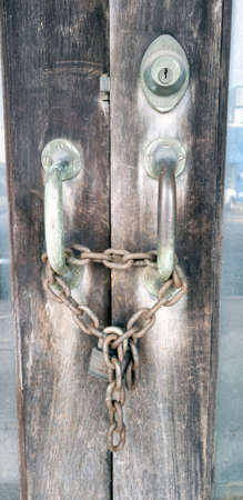 Aged door handles chained closed with antiqued padlock Stock Photo