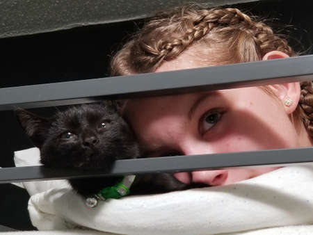 Closeup of blonde girl with braids and black cat Stock Photo
