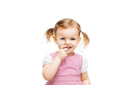 Preschool toddler girl looking through magnifying glass