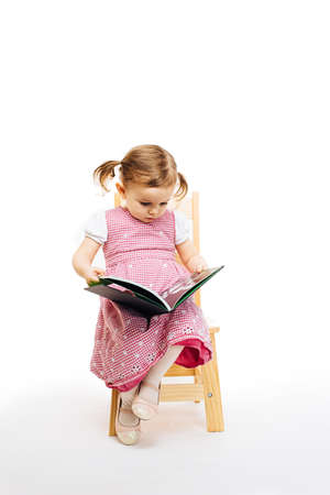 toddler girl reading a book sitting on a chair, white background