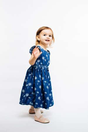 彼女の腕のさよならやこんにちは手を振る小さな幼児の女の子