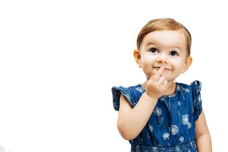 happy and curious toddler girl thinking with a finger on her mouth Banco de Imagens