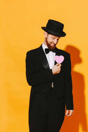 Hopeful smiling man with top hat holding a pink heart, be my valentine