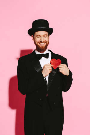Smiling man in a tuxedo and top hat holding a red heart