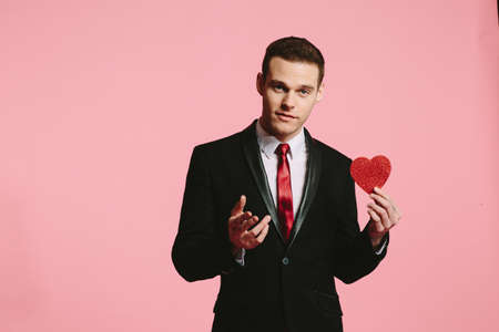 Handsome man in a black suit holding a red heart for Valentine's Day