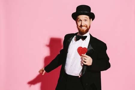 Smiling and dancing man in a tuxedo and top hat holding a red heart Banque d'images - 105635429