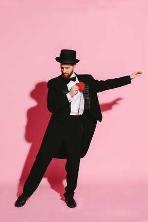 dancing man in a tuxedo and top hat holding a red heart Banque d'images