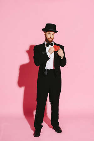 Serious man in a tuxedo and top hat holding a red heart