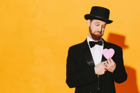 Sad man with top hat holding a pink heart, be my valentine
