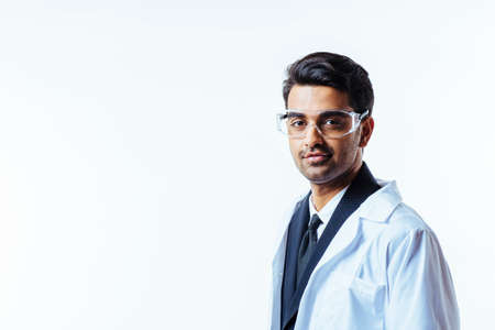 Portrait of a serious man in business suit, lab coat and protective glasses, isolated on white studio background Stok Fotoğraf